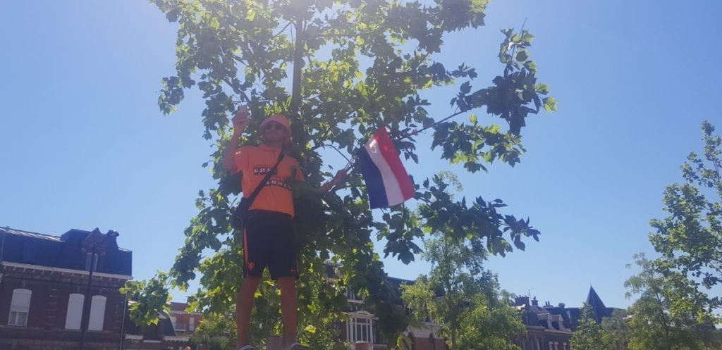 A lone Dutch supporter dressed in orange stands by a tree holding a Dutch flag for the 2019 FIFA Womens World Cup.