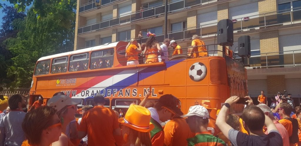 An orange double-decker bus is surrounded by Dutch fans at the 2019 FIFA Womens World Cup.