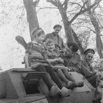 604px-Kinderen_in_klederdracht_op_een_Canadese_pantserwagen,_Bestanddeelnr_900-2853