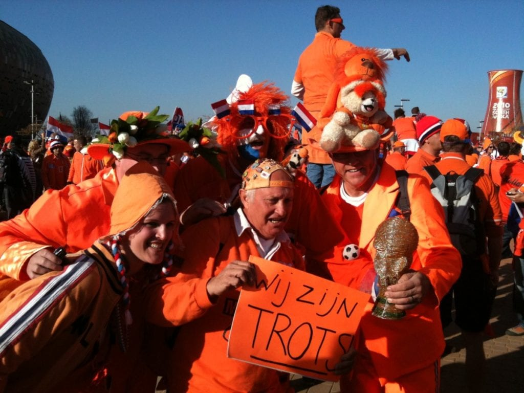 Dutch football fans dressed in orange in crazy costume.