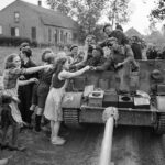 A_carrier_crew_of_8th_Rifle_Brigade_hands_out_chocolate_to_Dutch_civilians_during_the_advance_of_11th_Armoured_Division_in_Holland,_22_September_1944._B10245
