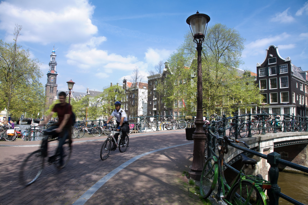 photo-two-people-on-bikes-turning-a-corrner-by-a-bridge-in-amsterdam