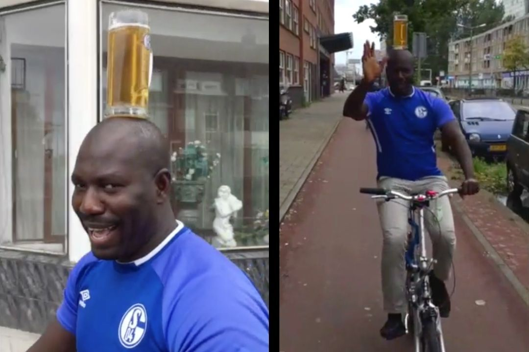 Man-cycles-with-beer-on-head