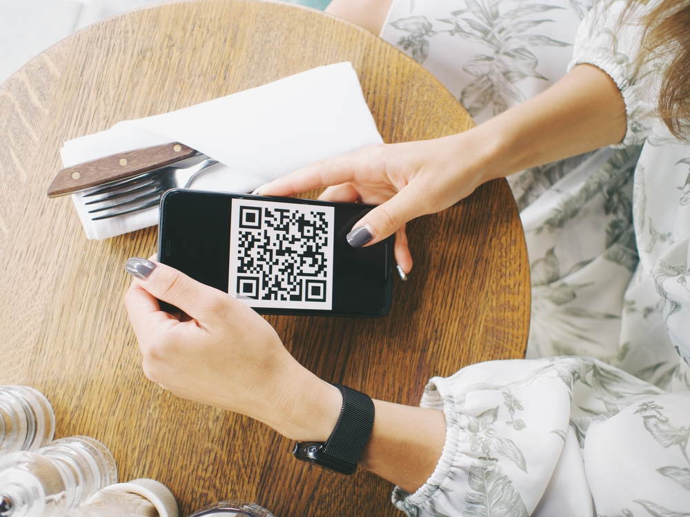 Woman-holds-smartphone-with-coronavirus-QR-code-in-cafe