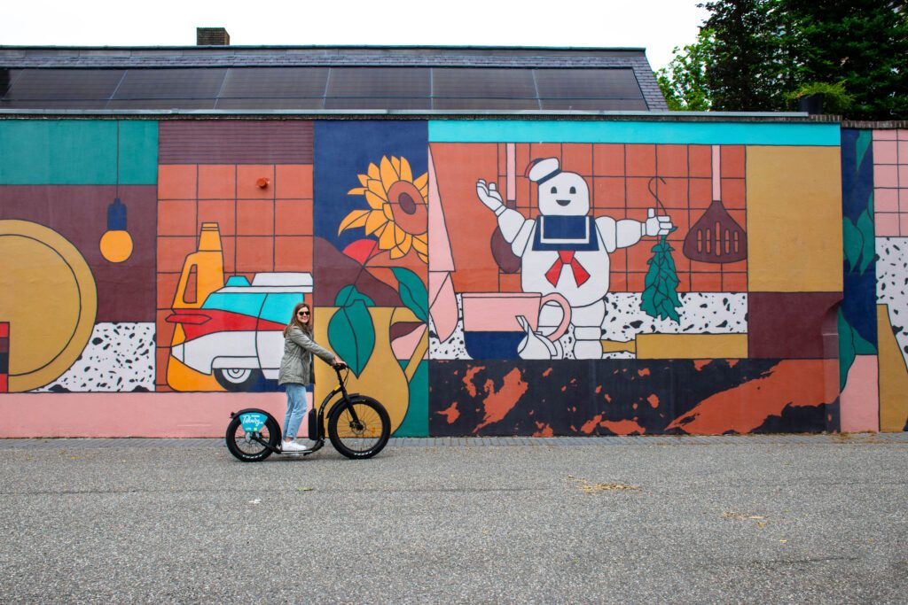 photo-of-a-girl-on-an-e-step-in-front-of-a-mural-in-tilburg