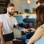 Couple making payment with smartphone at coffe shop