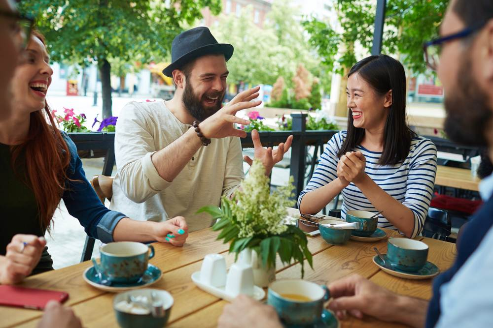 photo-guy-teling-funny-story-to-his.group-of-friends-while-sitting-at-a-cafe-in-the-netherlands