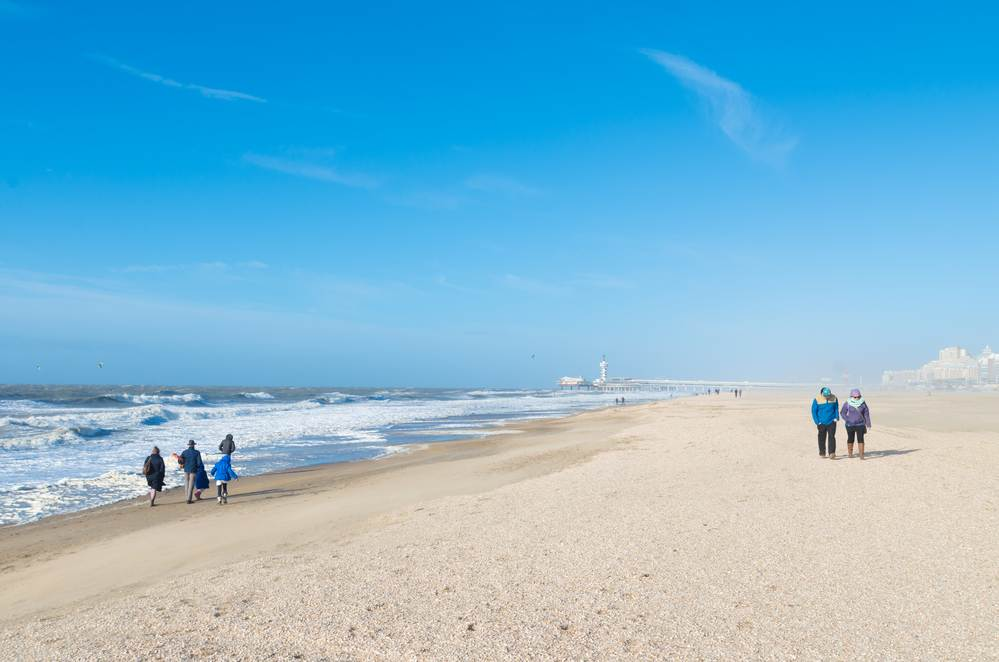 people-strolling-along-sunny-Dutch-beach-in-warm-weather
