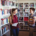 Classmates interacting with each other in library