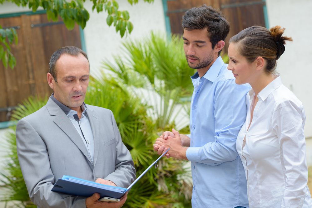 Photo-of-couple-discussing-bidding-on-house-in-Netherlands-with-selling-realtor
