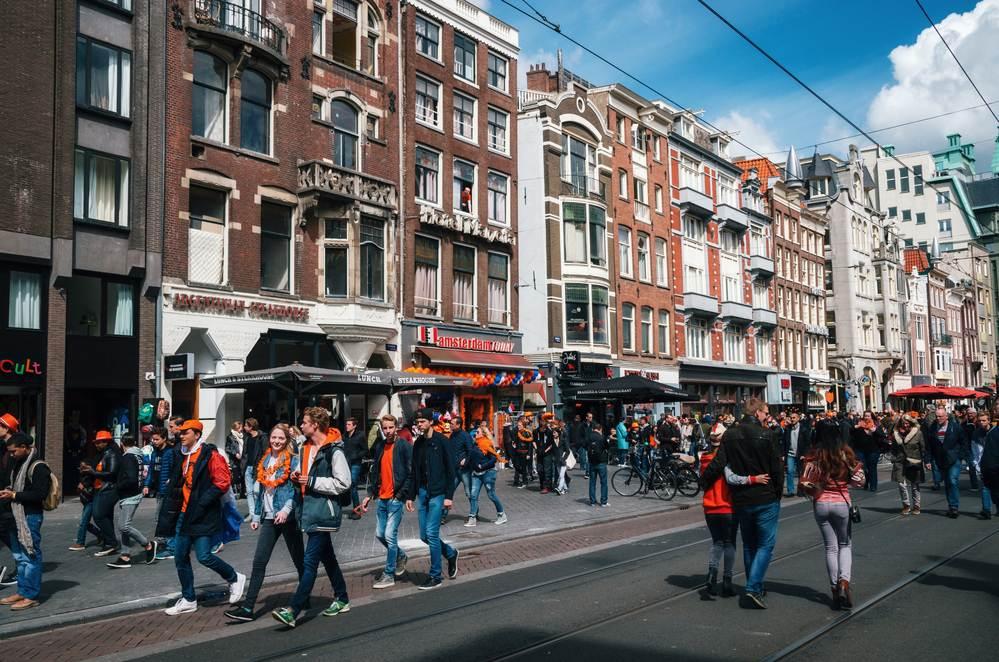 photo-dutch-people-dressed-in-orange-walking-down-a-street-in-the-netherlands