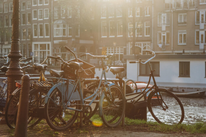 photo-sun-shining-on-bikes-parked-by-a-canal-in-the-netherlands