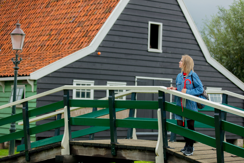 Woman-standing-on-bridge-looking-at-houses-in-Netherlands