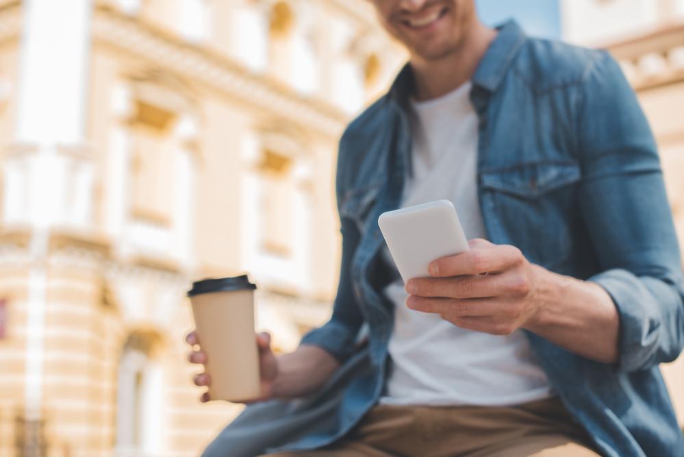 Photo-of-man-using-Raisin-savings-account-on-phone-Netherlands