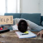 Young desperate student in stress working and studying holding a help sign.