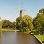 Panoramic photo of dutch city Leiden in summer. Canal and windmill.