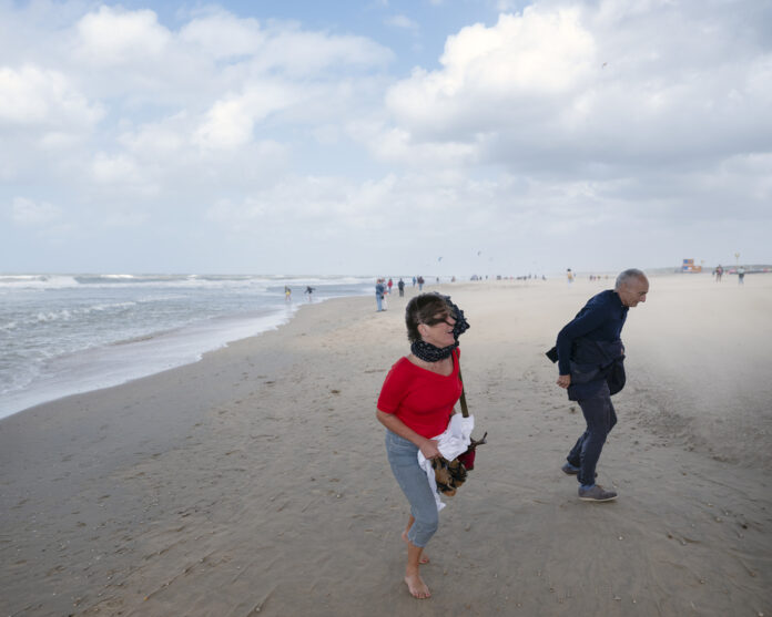 Photo-of-people-walking-on-Dutch-beach-during-strong-winds