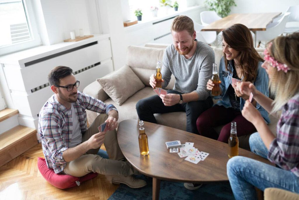 photo-of-a-happy-group-of-friends-playing-cards-and-drinking