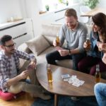 Group of happy friends playing cards and drinking