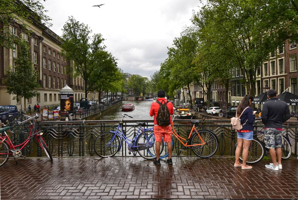 couple-stands-on-a-bridge-in-amsterdam-on-a-rainy-day-in-June