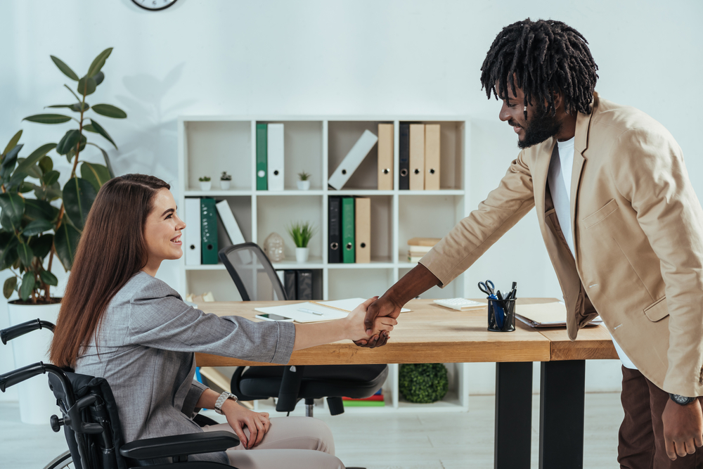 Photo-of-woman-in-wheelchair-shaking-hands-with-interviewer-at-job-interview-in-the-Netherlands