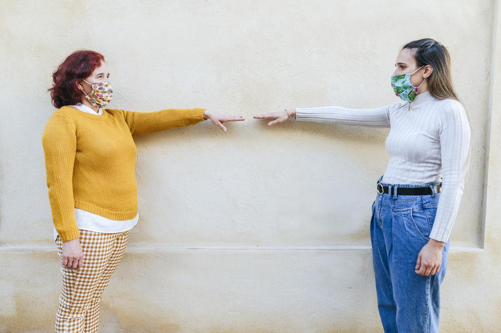photo-two-women-wearing-masks-illustrating-social-distancing