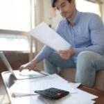 Young man mange household finances paying bills online