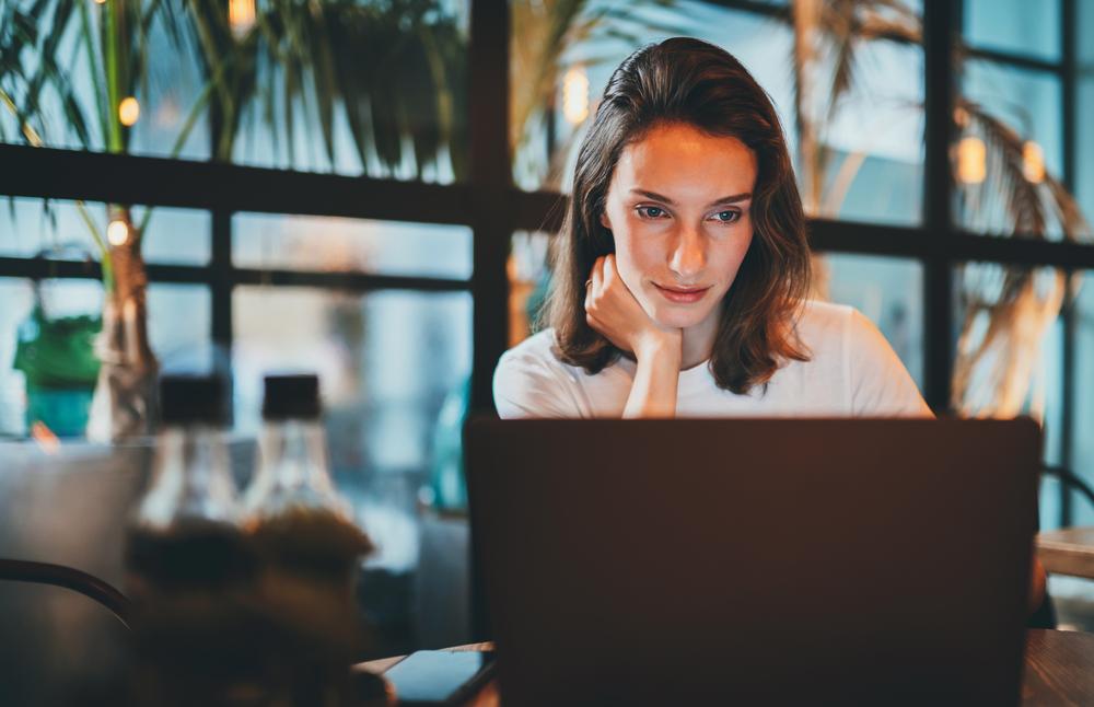 Photo-of-woman-sitting-at-desk-looking-at-laptop-using-Raisin-banking-online-savings-platform-in-Netherlands