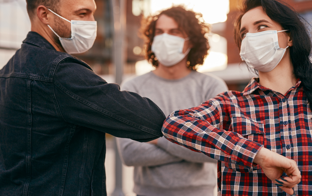 photo-young-people-wearing-masks-and-greeting-each-other-with-elbows