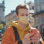 Caucasian urban guy student with blonde hair typing on smartphone messaging while walking on street with protective face mask against coronavirus. Pandemic.