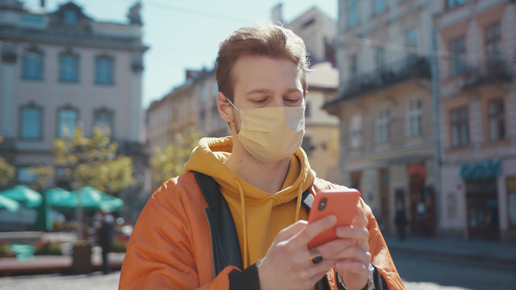 photo-dutch-young-man-with-facemask-looking-at-his-phone