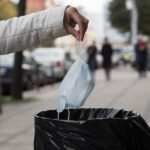 A woman throws a facemask at a public trash can on a city street