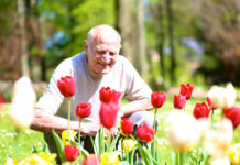Photo-of-old-Dutch-man-smiling-at-flowers