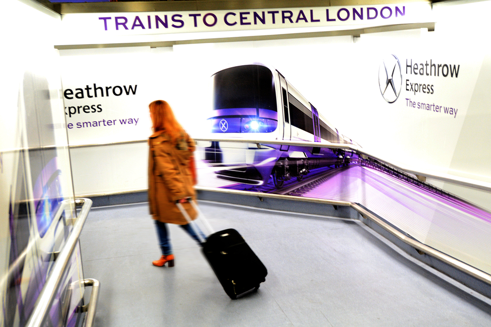 photo-woman-with-trolly-arriving-in-heathrow-airport-headed-for-the-train-station