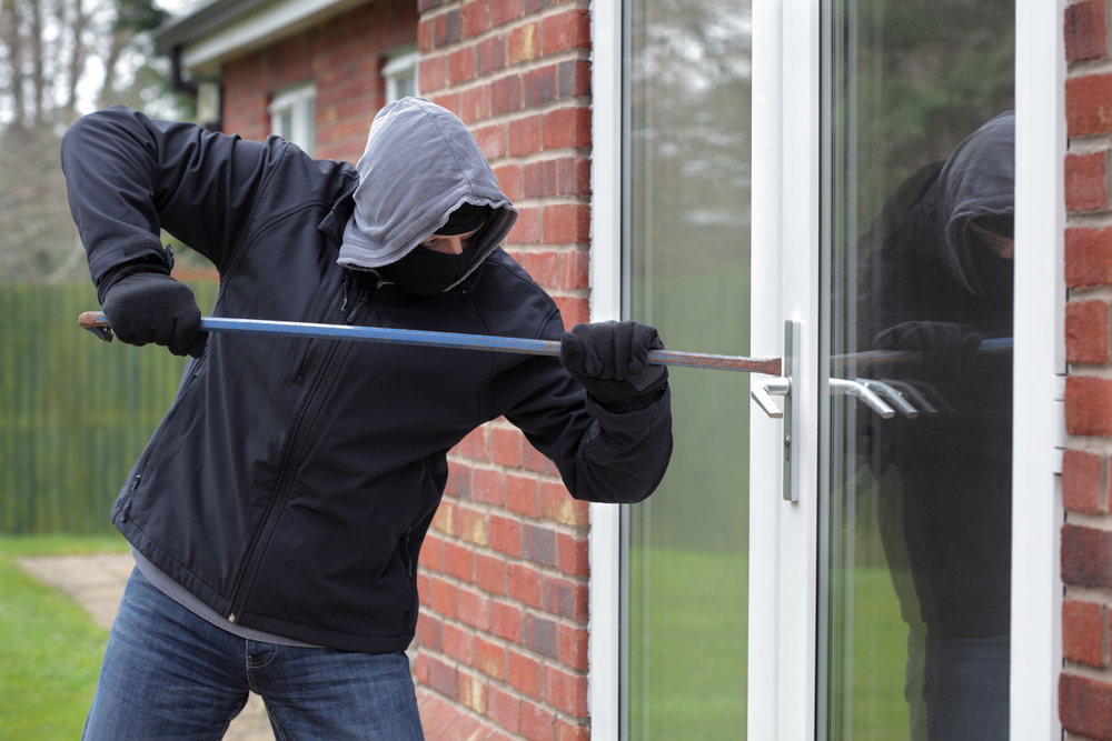Burglar-breaking-into-a-house-window-with-a-crowbar