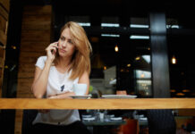 Concerned-blonde-woman-answers-phishing-call-in-cafe