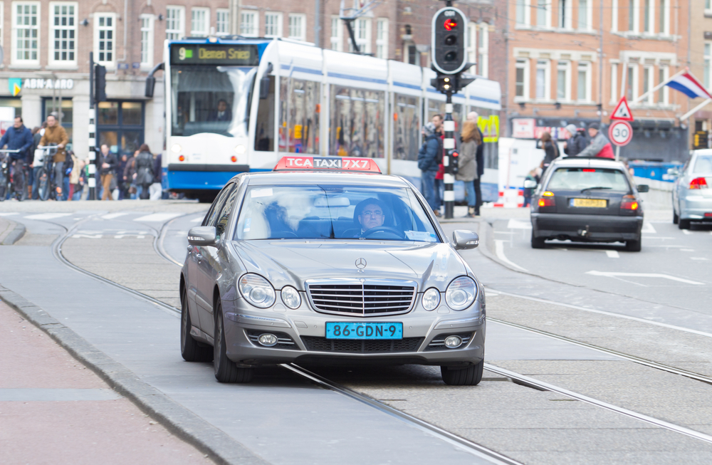 Taxi-driving-through-central-AMsterdam-in-front-of-a-tram