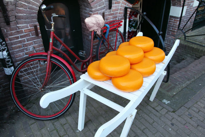 Dutch cheese on a cart for sale next to a bike.