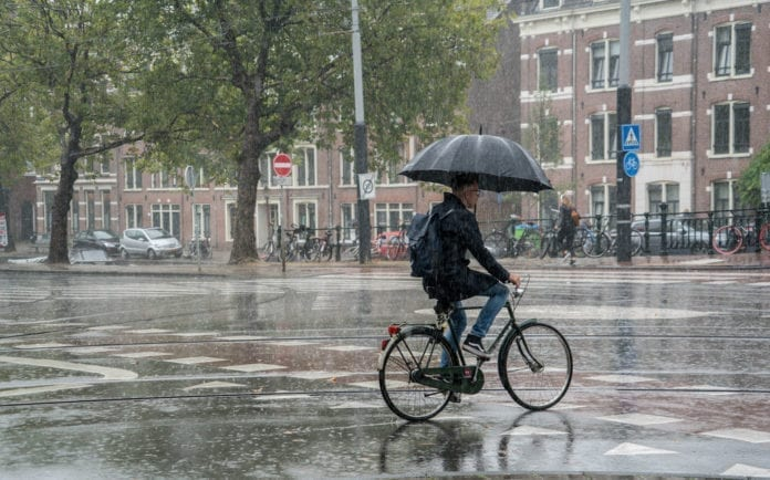 photo-of-man-biking-with-an-umbrella-in-the-netherlands