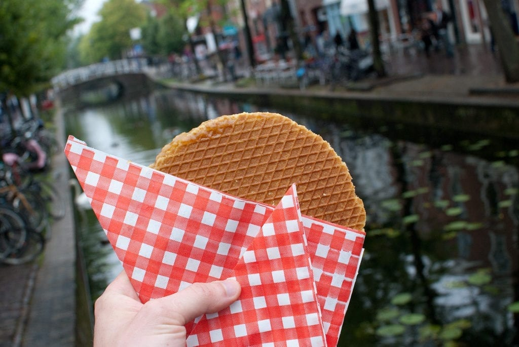 Stroopwafel held in front of a canal in Amsterdam