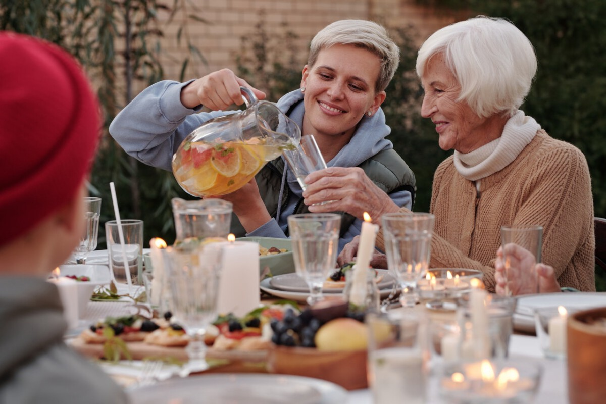 Dutch-woman-pouring-a-drink-for-her-grandmother-outside-on-Wit-Sunday