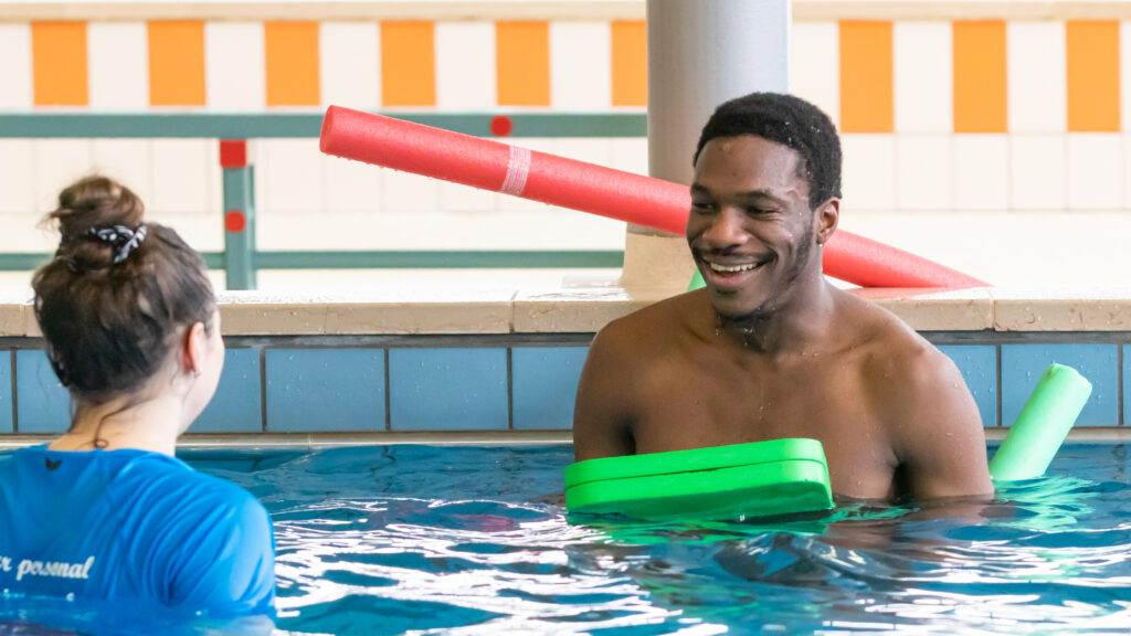 Photo-of-man-learning-how-to-swim-with-your-personal-swim-coach-staff-member-in-pool