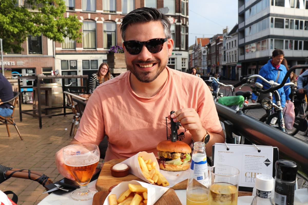 Photo-of-man-eating-burger-at-restaurant-Leiden