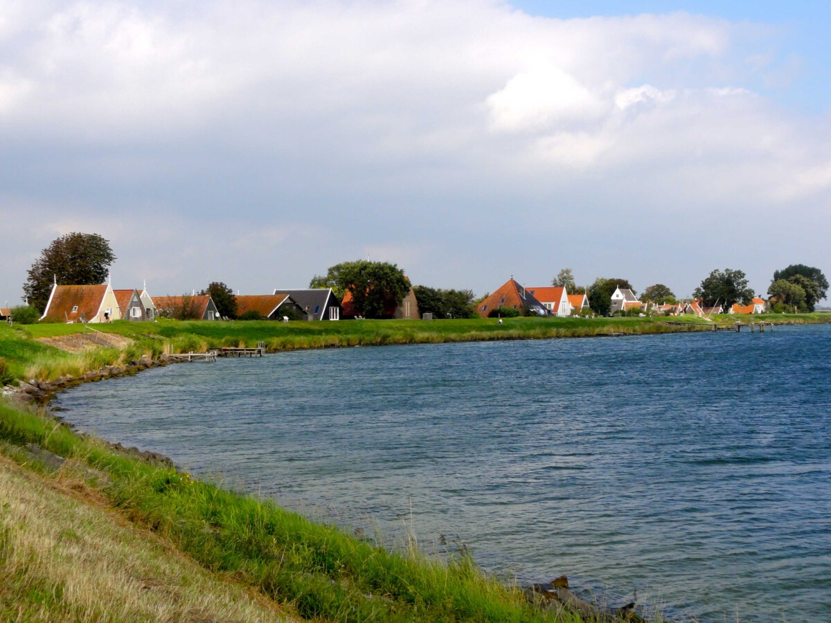 A row of houses curves around the bank of a lake.