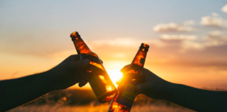 A-British-person-and-a-Dutch-person-clinking-beer-bottles