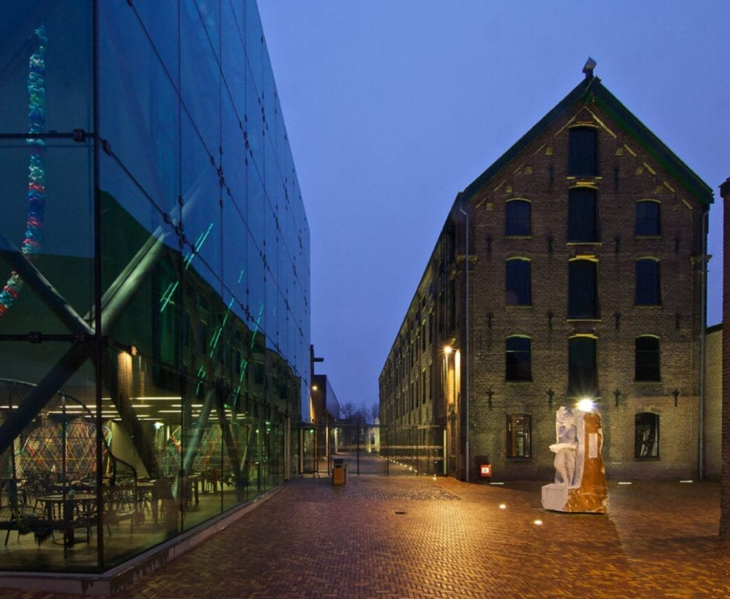 the Textiel museum at night: modern glass building and a heritage warehouse