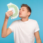Greed and money. Young businessman in casual white t-shirt smell