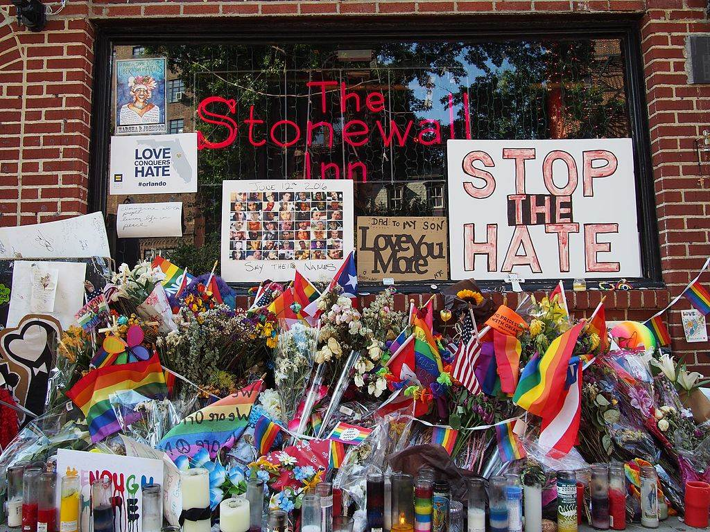 Photo-of-stonewall-Inn-with-gay-flags-and-candles-commemorating-victims-of-violence-against-LGBTQ+-community