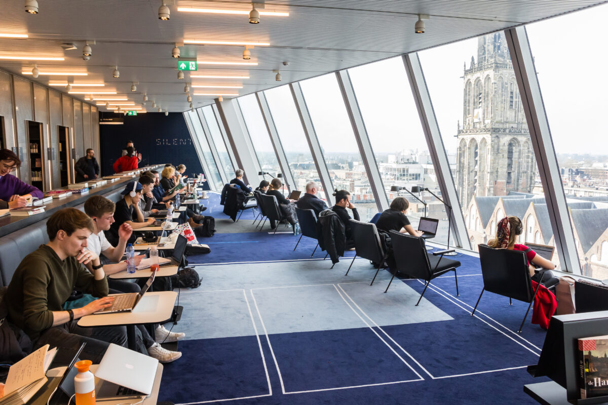 Students-working-in-the-library in-the-Groninger-Forum-with-view-over the-Martini-tower-in-The-Netherlands