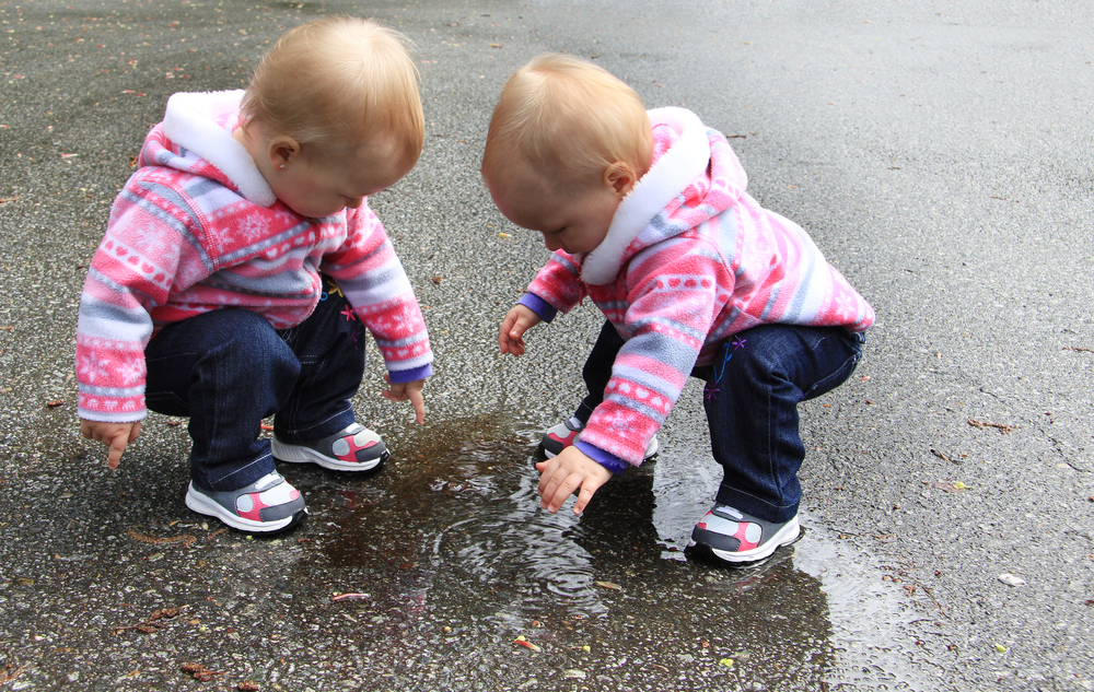 Twin-baby-girls-in-pink-coats-playing-in-puddle-of-water